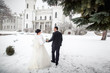Winter wedding, bride and groom walking in snowy weather at their wedding day
