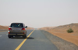 A car drives on an empty road in the deserts of Dubai, UAE