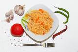 Рис с овощами в тарелке, плов.