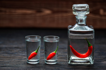 vodka with chili peppers on wooden table, selective focus
