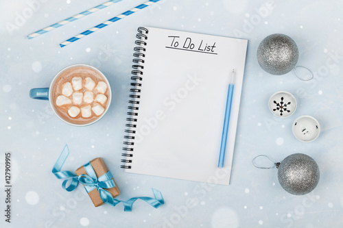 Poster Cup of hot cocoa, gift, holiday decorations and notebook with to do list on blue vintage table from above, christmas planning and mockup