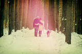 Young hugging couple in love with dog on the leash walking outdoor in winter forest at sunset