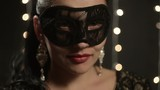 woman in a Venetian mask on the background of night lights, close-up