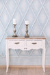 white dresser in the light room and candlesticks from silver. An interior in classical style