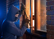 Постер, плакат: Burglar Using Crowbar To Break Into a House at night with room left and right for type