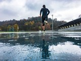 Man running on athletic track in a rainy day