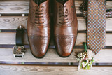 Accessories of a groom: shoes, boutonniere, tie and clock on a wooden surface