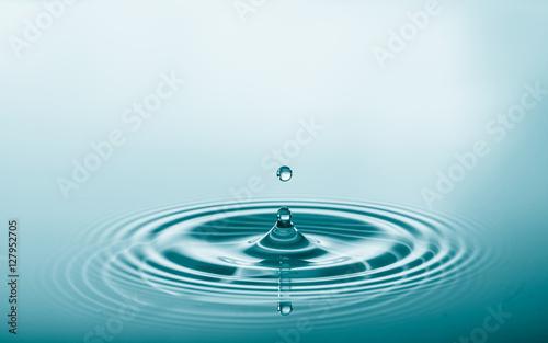 Kropla wody spada i kapie na lustrze wody. Powitalny plusk wody i doskonałe kręgi na powierzchni wody