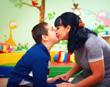 mother kissing her beloved son with disability in rehabilitation center, soulful moment