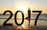 Happy new year card 2017. Silhouette of A girl doing Yoga vrikshasana tree pose on tropical  beach with sunset sky background, watching the sunset, standing as a part of the Number 2017 sign.