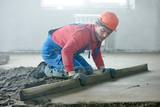 worker screeding indoor cement floor with screed - 127971522