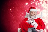 Fototapety Composite image of happy santa claus messaging with mobile phone