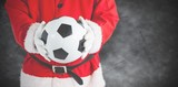 Composite image of santa claus holding a football - 127997791