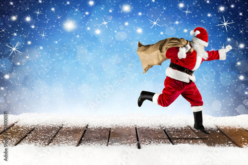 late santa claus running over wooden planks in front of snowy blue stars bokeh night sky background