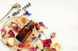 Various bright medicinal herb plant on wooden plate, essential oil extract bottle, top view. Botanical cosmetic ingredients, aromatherapy background. Herbal pharmacy.