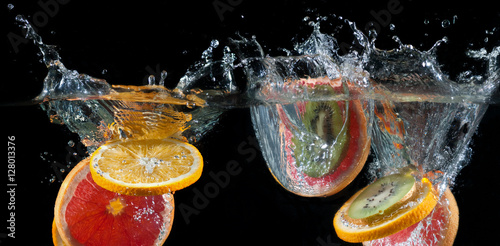 Orange, lemon, grapefruit and lime splashing into water - 128013376