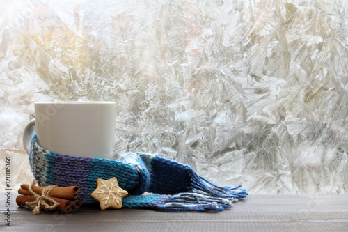 Poster warming drink on a winter day/ large white mug with blue scarf standing on a tab