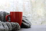 warming moments winter holidays/ cozy soft gray blanket with a big red cup on the background of a window decorated with frost