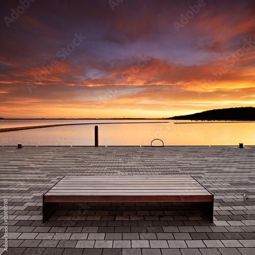 Poster Sitzbank im Hafen bei Sonnenaufgang