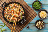 Rice noodles with chicken, mushrooms mun and vegetables in wook. - 128022969