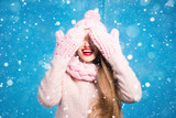 Winter portrait of a beautiful woman clothing her eyes with knitted gloves standing on the blue background