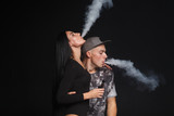 a man and woman smoking electronic cigarette