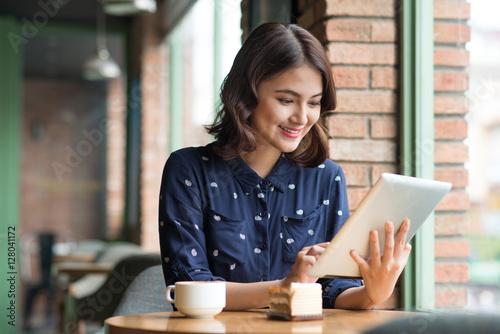 Fototapeta Beautiful cute asian young businesswoman in the cafe, using digi