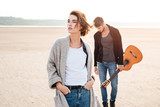 Beautiful young couple standing at the seashore with guitar - 128043995