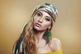 Beauty portrait of a beautiful girl in a scarf with a bright golden Arabic makeup on a beige background.
