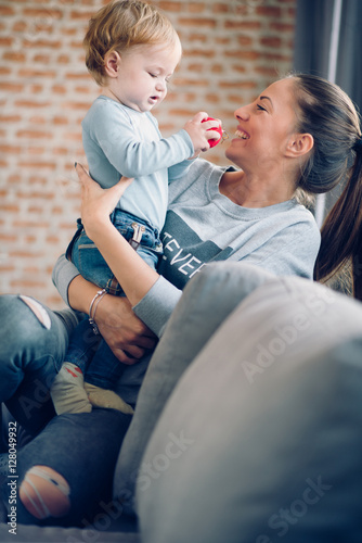 Fotografiet Mom playing with her son in cosy living room