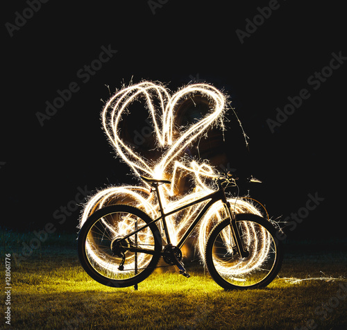 Poster Silhouette of mountain bicycle on Green meadow with Beautiful Fireworks sparkler