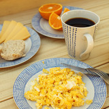 Scrambled eggs, coffee, breakfast on the wooden table