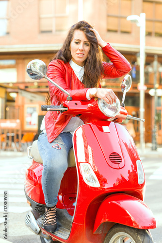 Poster Young girl with red jacket riding on her red scooter