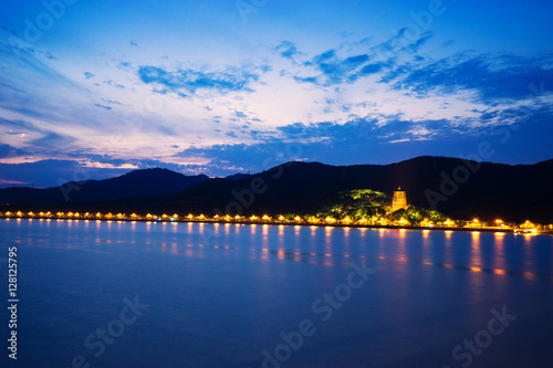 Poster illuminated tower near hill by river at twilight
