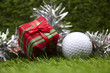 Present for golfer, golf ball and gift box on green grass background
