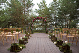 Beautiful wedding ceremony outdoors. Decorated chairs stand on t - 128142337