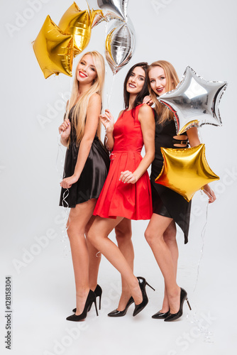 Poster Full length of three smiling women with star shaped balloons