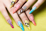 Long beautiful manicure in pop-art style on female fingers. Nails design. Close-up.