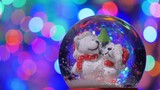 Christmas snow globe with cheerful polar bears, with new year tree lights twinkling.