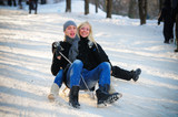 young man and woman on a sled