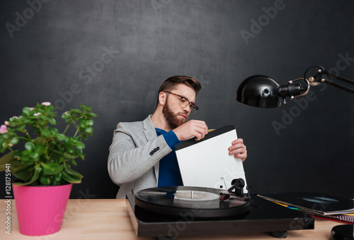 Poster Focused bearded young businessman using turntable and vinyl record