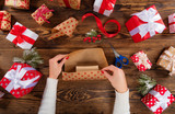 Woman packing Christmas presents on wooden table background