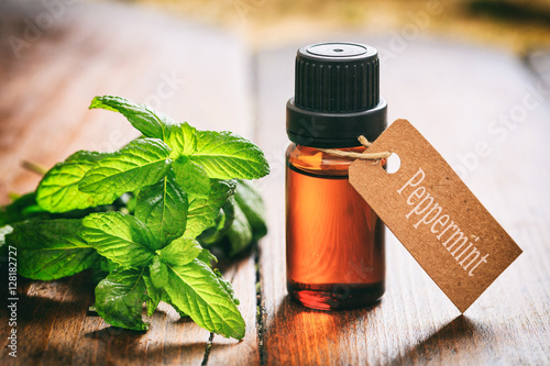 Fresh peppermint and oil on wooden background