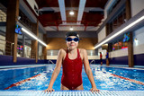 Girl child swimmer in a red bathing suit on a background of the