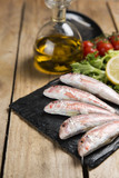 raw red mullet served on curly salad on slate plate on wooden table