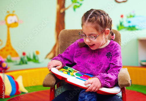 Fotografiet cute girl in wheelchair playing with developing toy in kindergarten for children