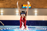 Girl swimmer in a red bathing suit, hat, glasses jumping out of the water in the pool with a splash of spray indoors.