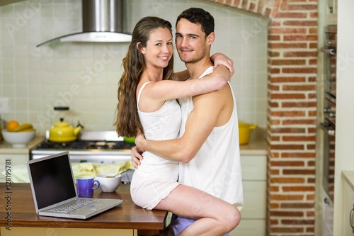 Foto op Aluminium Milkshake Young couple cuddling on kitchen worktop