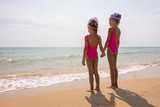 Two girls in bathing suits standing on the beach and look at the horizon