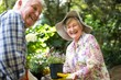 Happy senior couple with flower pots